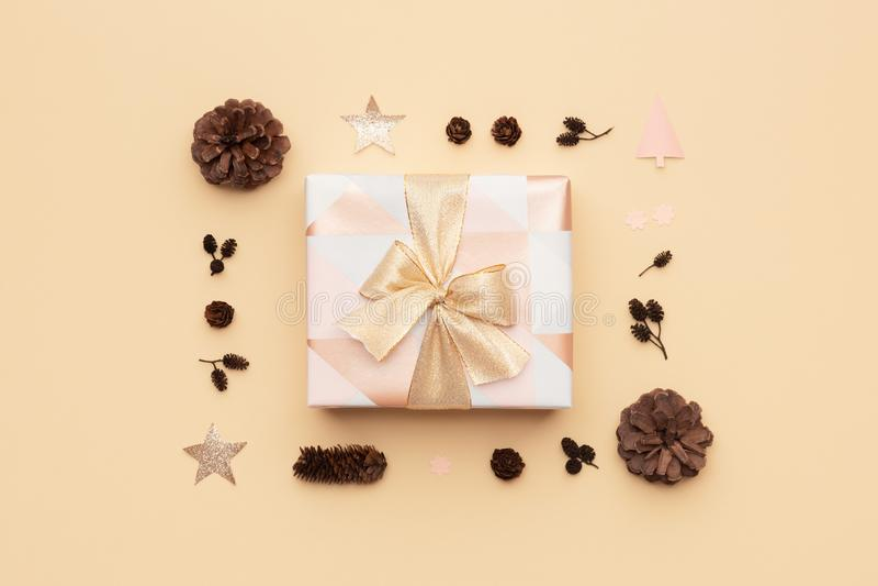Bello regalo di natale decorato con un arco del nastro isolato su fondo beige Rosa e scatola di natale avvolta oro fotografie stock libere da diritti