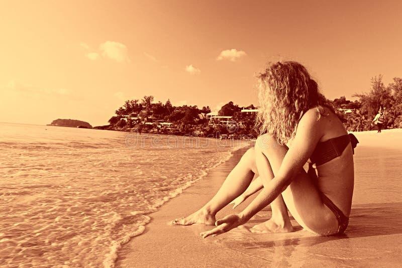 Bello resto riccio della ragazza sulla spiaggia immagine stock