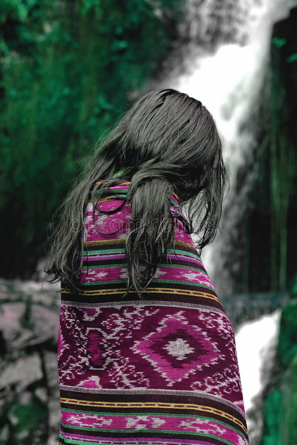 Bello ritratto asiatico della ragazza in coperta porpora davanti alla bella cascata naturale ed alla foresta verde fotografia stock libera da diritti