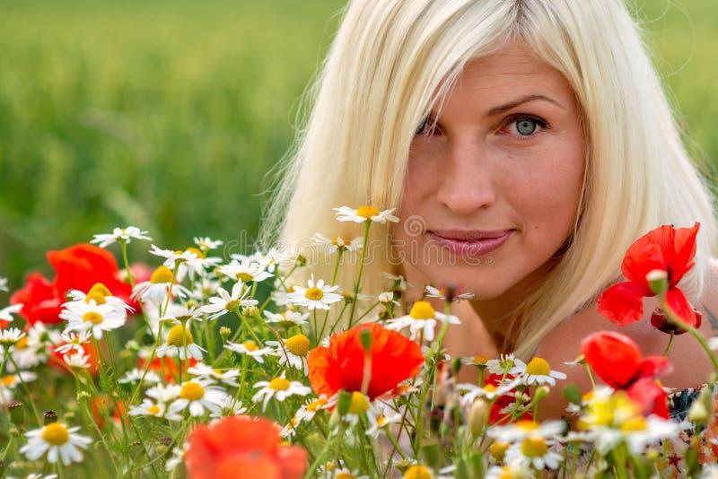 Bello, ritratto attraente e biondo della donna con i fiori del prato Fuoco molle fotografie stock