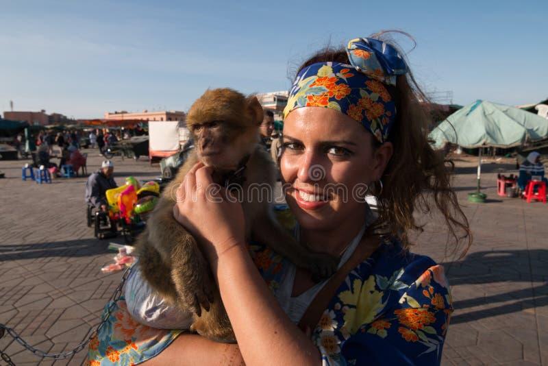 Bello ritratto castana della donna con un foulard e una scimmia nelle sue armi immagini stock