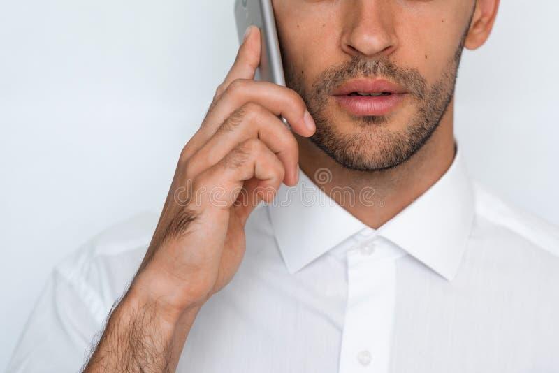Bello ritratto del primo piano del giovane facendo uso del telefono cellulare su fondo grigio Uomo d'affari che parla sul suo Sma fotografia stock libera da diritti