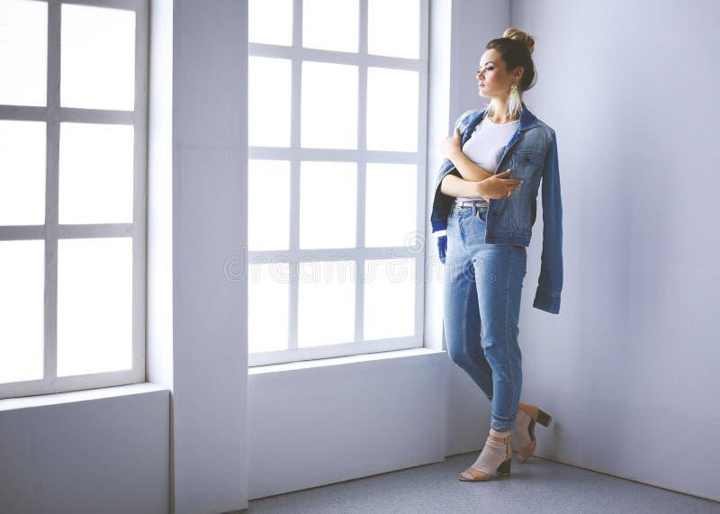 Bello ritratto della donna che sta finestra vicina Su fondo bianco fotografia stock