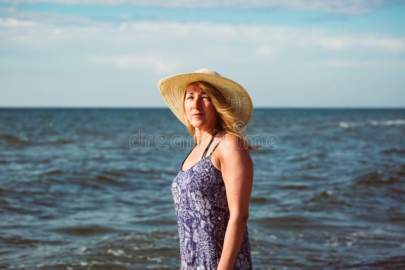 Bello ritratto della donna invecchiata media sulla spiaggia fotografia stock