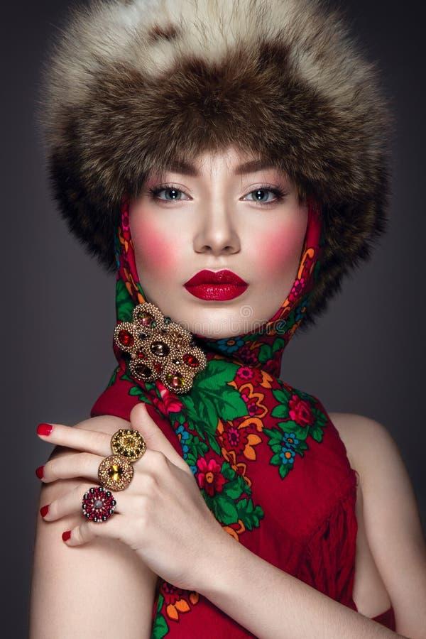 Bello ritratto della donna nello stile russo con il cappello e la sciarpa di pelliccia immagine stock