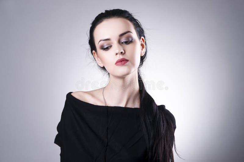 Bello ritratto della donna su un fondo grigio Trucco professionale fotografia stock