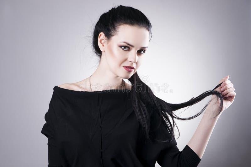 Bello ritratto della donna su un fondo grigio Trucco professionale fotografie stock