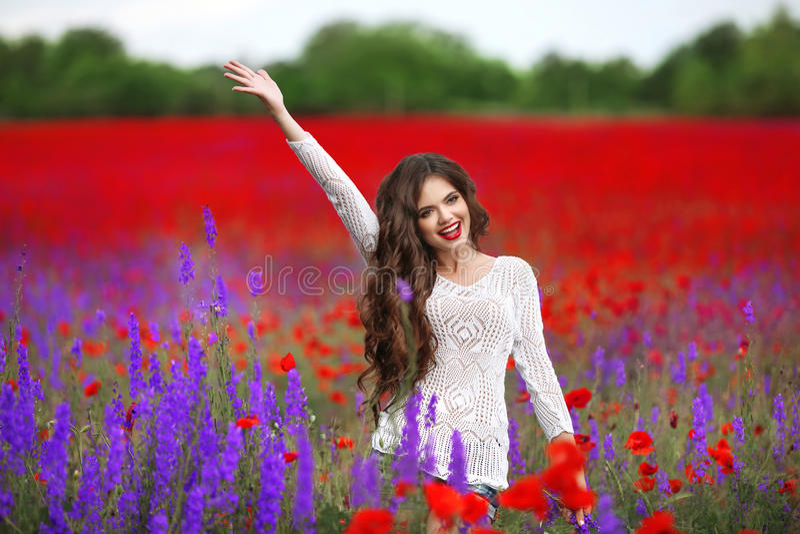 Bello ritratto della giovane donna nel campo dei papaveri Brun attraente immagini stock