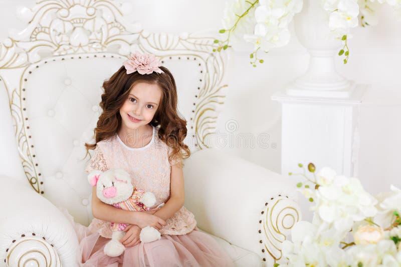 Bello ritratto della ragazza con il giocattolo luminoso che esamina i capelli scuri della macchina fotografica in riccioli sulla  immagine stock