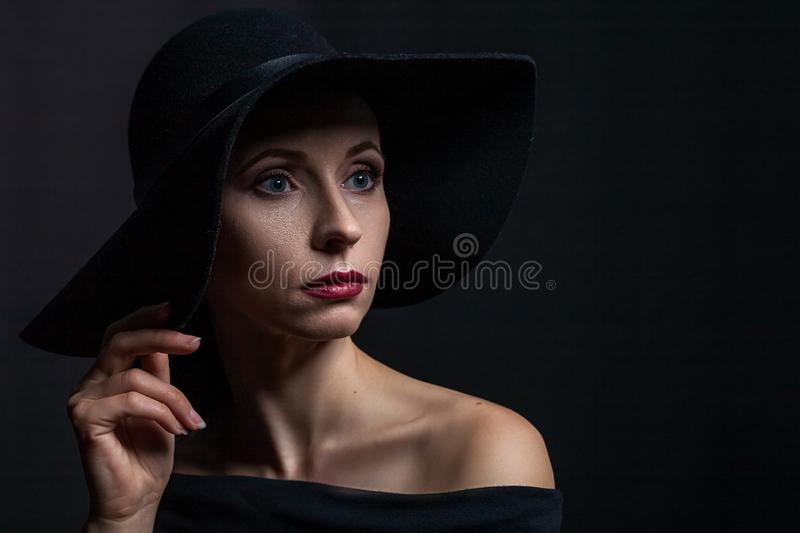 Bello ritratto di una donna in un black hat fotografie stock