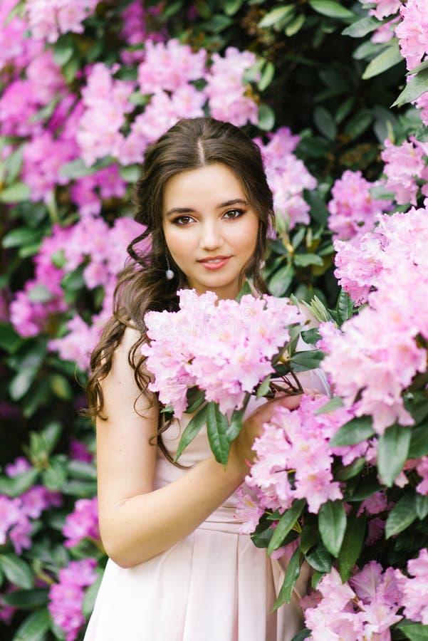 Bello ritratto di una ragazza adorabile che sta circondata dal rododendro di fioritura dei fiori rosa lilla in primavera nel giar fotografia stock