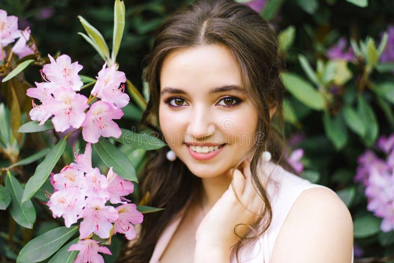 Bello ritratto di una ragazza adorabile che sta circondata dal rododendro di fioritura dei fiori rosa lilla fotografia stock