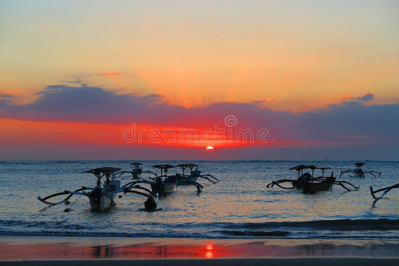 Bello rosa di tramonto o di alba del mare ed arancio con le barche tradizionali in Bali fotografia stock libera da diritti