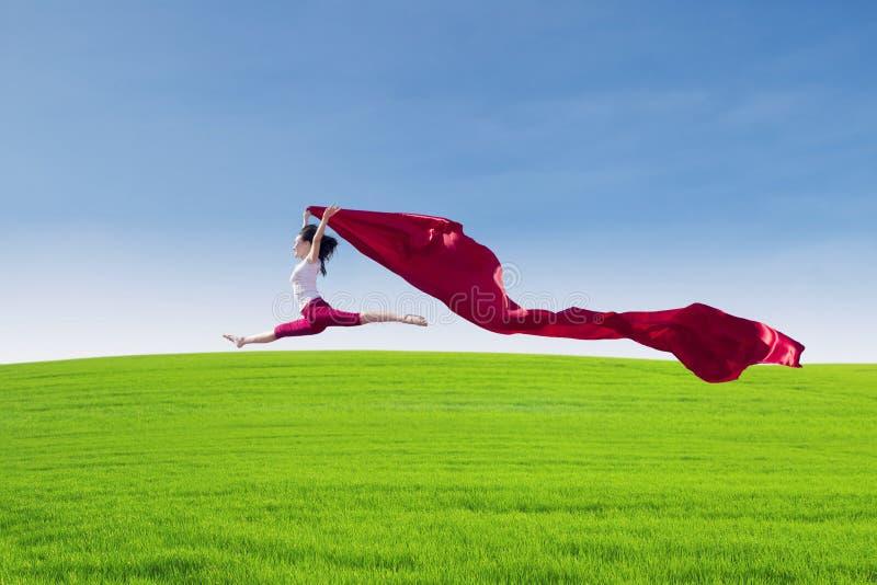 Bello salto femminile con la sciarpa rossa sul campo immagine stock libera da diritti