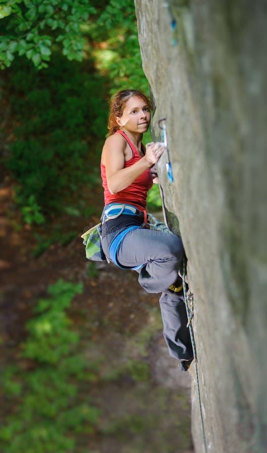 Bello scalatore della donna che scala roccia ripida con la corda fotografia stock