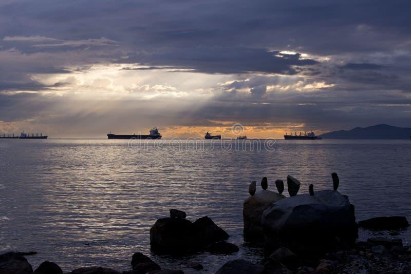 Bello scatto del mare con pietre equilibrate sulla roccia vicino alla costa immagine stock libera da diritti