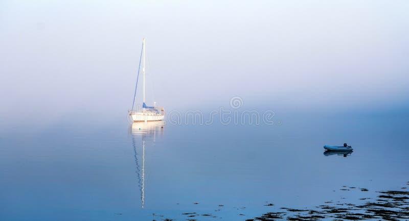 Bello scatto di uno sloop uscito dalla nebbia mattutina nel porto di Northwest nell'isola di Deer fotografia stock