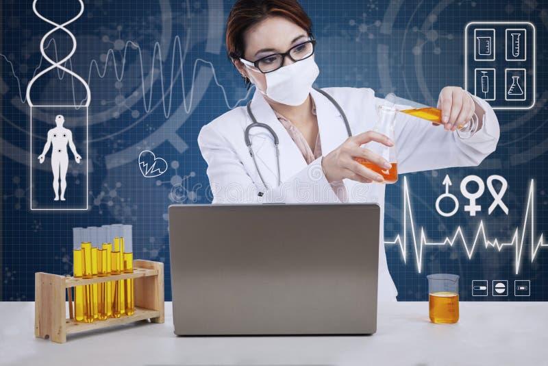 Bello scienziato che analizza liquido con il computer portatile immagine stock libera da diritti
