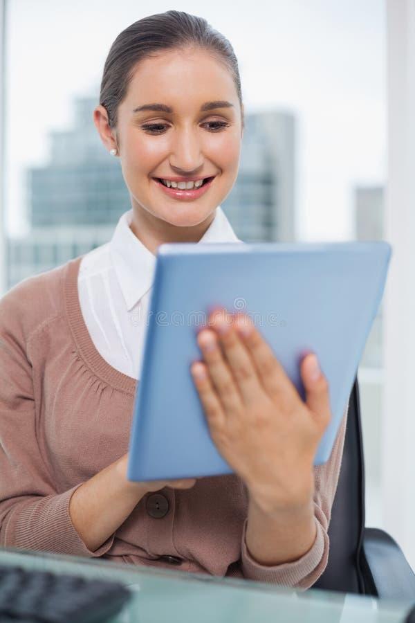 Bello scorrimento felice della donna di affari sulla sua compressa fotografia stock libera da diritti