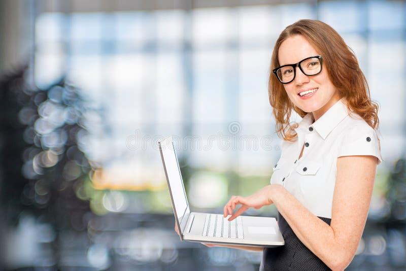 Bello segretario esile con un computer portatile fotografia stock