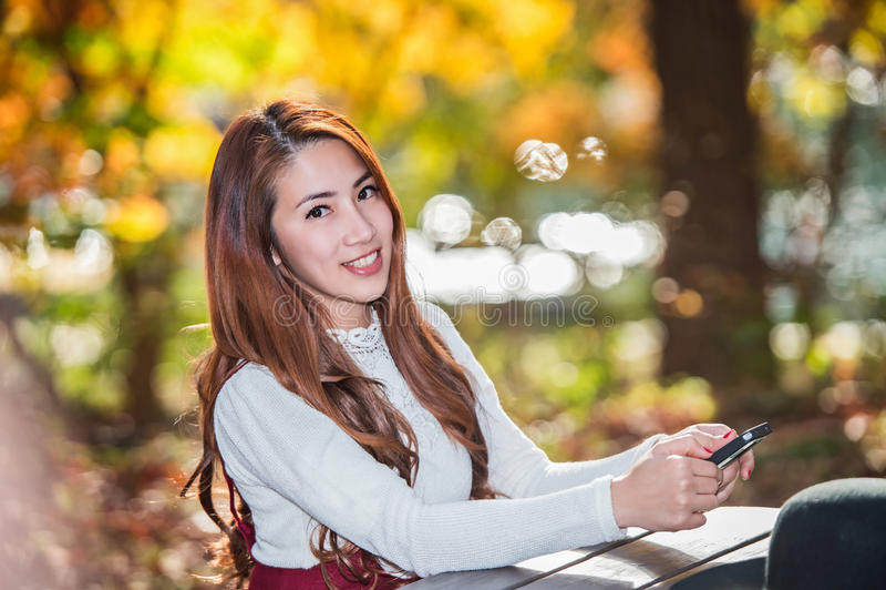 Bello smartphone sorridere della donna e della tenuta della mano fotografia stock