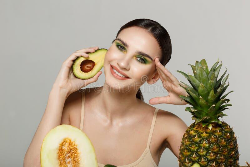 Bello sorridere castana sano della ragazza, esaminante la macchina fotografica con l'avocado a disposizione vicino al fronte immagini stock
