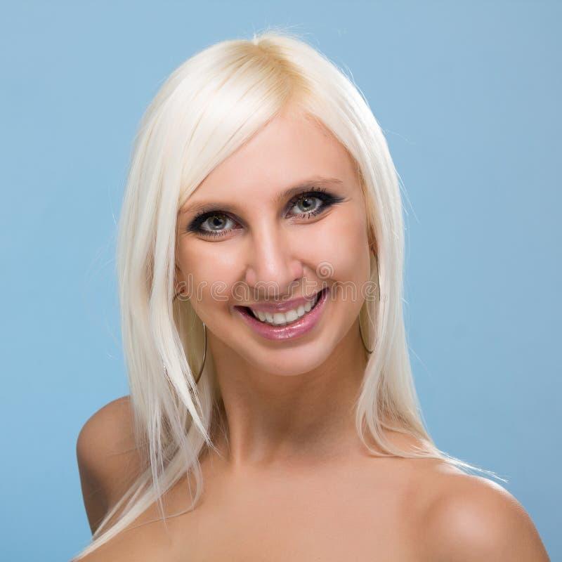 Bello sorridere del ritratto della donna isolato sopra un blu immagine stock