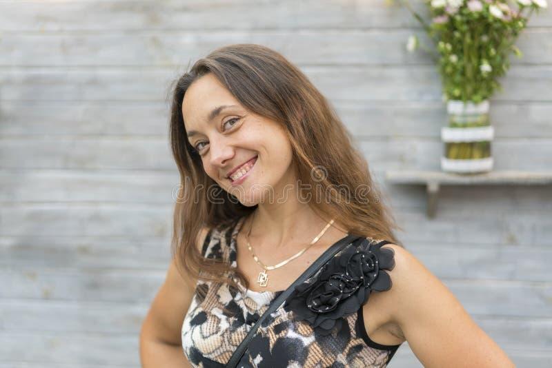 Bello sorridere della giovane donna su priorità bassa grigia Ragazza attraente felice che controlla fondo grigio e che esamina immagini stock libere da diritti