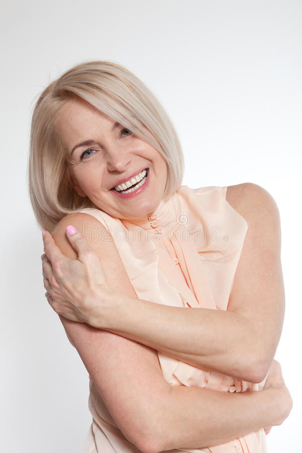 Bello sorridere di mezza età attivo della donna amichevole e esaminare la macchina fotografica fine del fronte della donna in su immagine stock