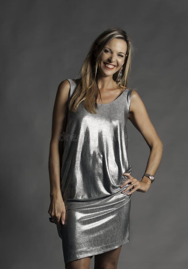 Bello sorridere, donna più anziana bionda con gli orecchini d'argento e vestito metallico immagini stock libere da diritti