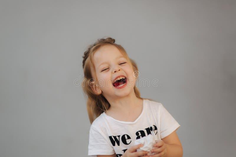 Bello sorriso della bambina alla macchina fotografica Fondo grigio siamo tutti i bambini fotografie stock libere da diritti
