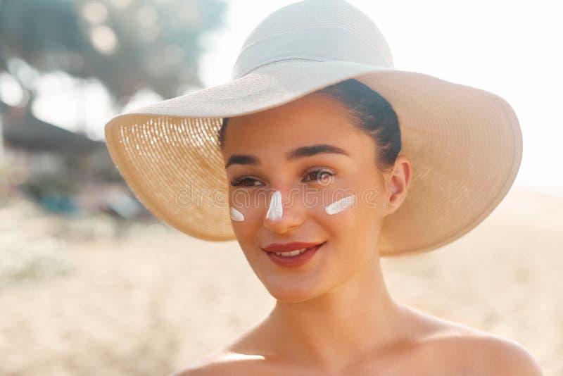 Bello sorriso della donna che applica la crema del sole sul fronte Skincare immagine stock