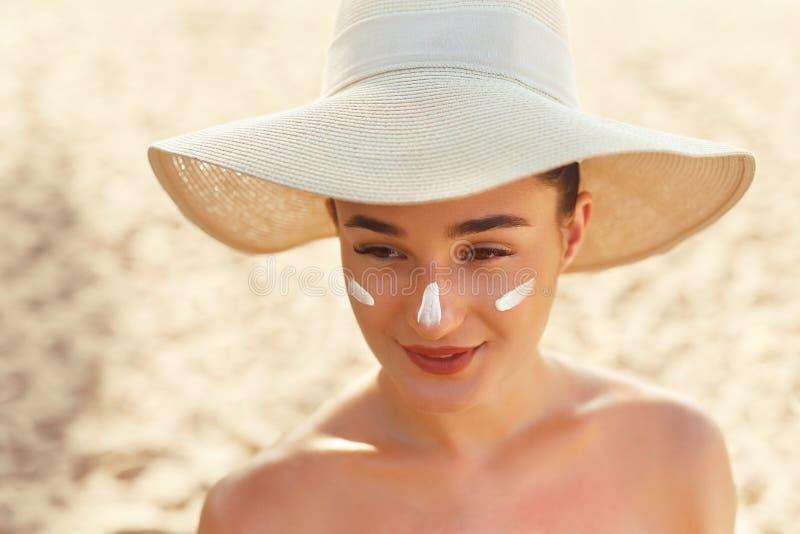 Bello sorriso della donna che applica la crema del sole sul fronte Skincare Protezione di Sun del corpo fotografia stock libera da diritti