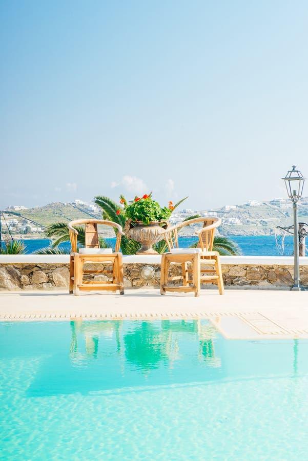 Bello stagno con le sedie vicino al mare sull'isola di Mykonos i fotografia stock libera da diritti