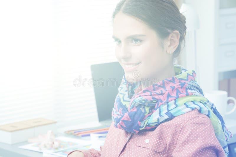 Bello stilista che si siede allo scrittorio in studio immagine stock