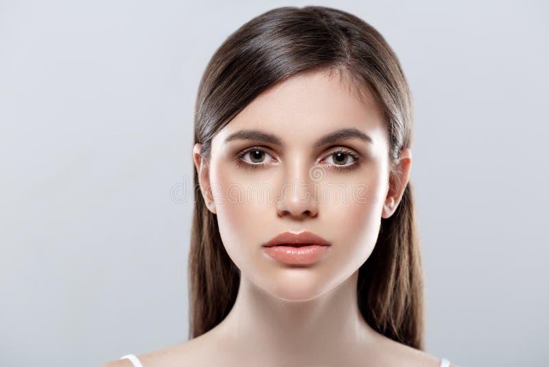Bello studio del fronte della donna su bianco con le labbra sexy su fondo grigio immagini stock