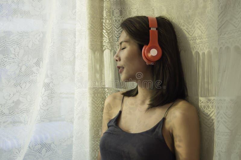 Bello supporto asiatico della ragazza che ascolta la musica dalla finestra della camera da letto, mattina con luce solare morbida fotografia stock