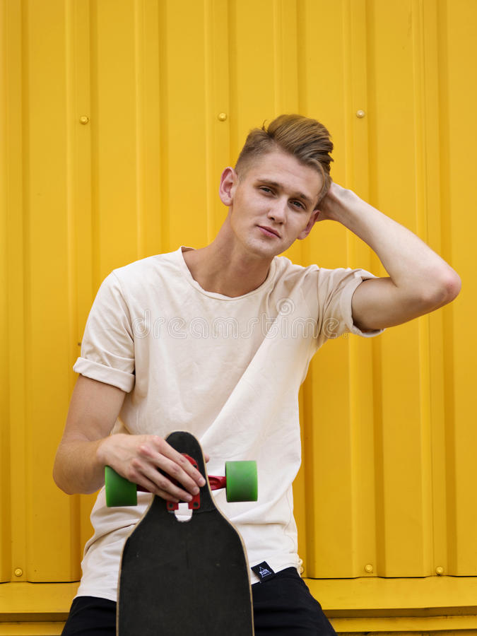 Bello teenager con un pattino Giovane tipo attraente che tiene un pattino su un fondo giallo della parete concetto della gioventù immagine stock