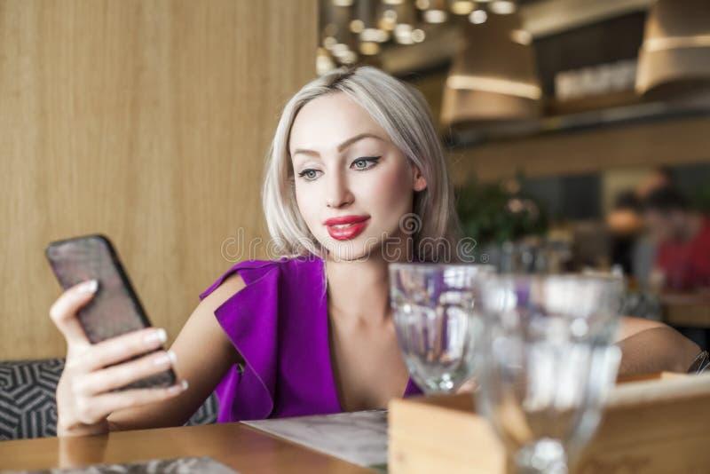 Bello telefono cellulare del wiith della donna in caffè immagini stock