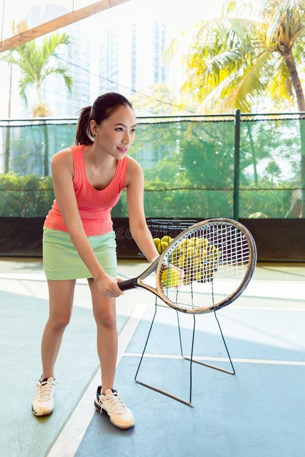 Bello tennis asiatico che tiene la racchetta e la palla prima del servire fotografie stock libere da diritti
