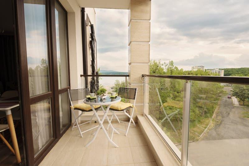 Bello terrazzo o balcone con la tavola con le tazze ed il fiore di caffè e sulle sedie Balcone con la vista del mare circondato d fotografia stock libera da diritti
