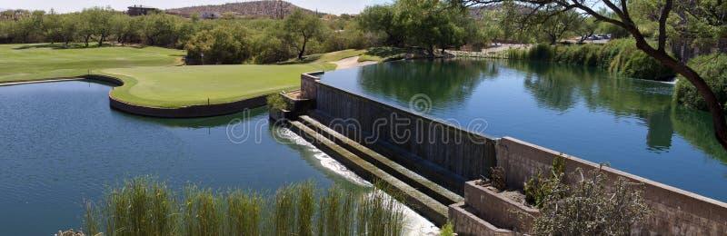 Bello terreno da golf del deserto con la cascata del lago immagini stock