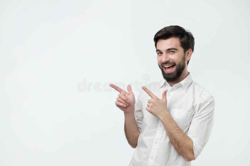 Bello tipo barbuto felice che esamina macchina fotografica, sorridente ed indicante da parte con la mano immagini stock libere da diritti
