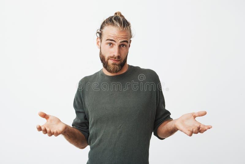 Bello tipo maturo unshaved con taglio di capelli alla moda in panno grigio che guarda in camera, diffusioni le sue mani con colpe fotografia stock