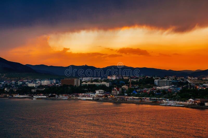 Bello tramonto e la città dal mare fotografia stock libera da diritti