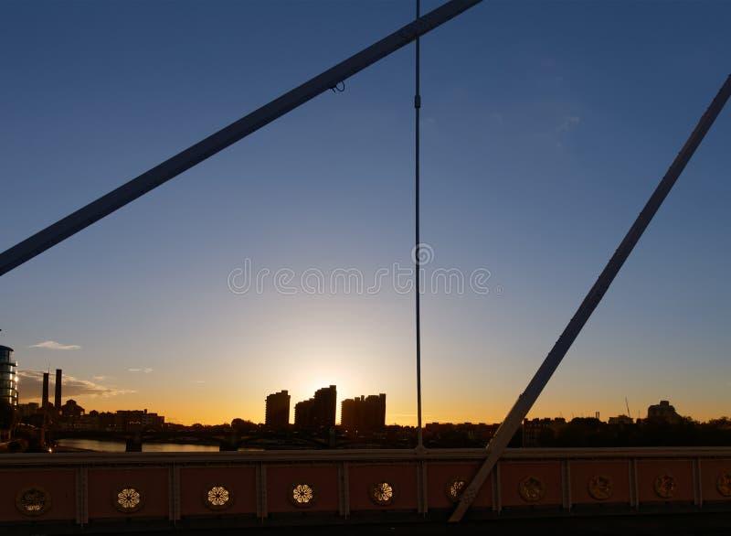 Bello tramonto, la siluetta delle costruzioni e strutture d'acciaio di un ponte immagini stock