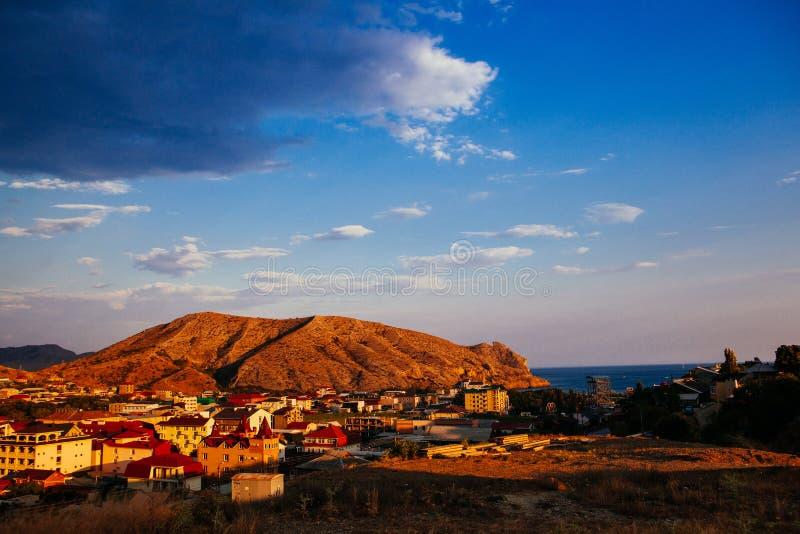 Bello tramonto nella sera e montagne vicino alla città immagine stock libera da diritti
