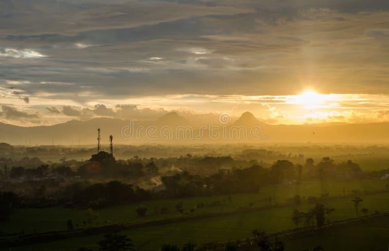 Bello tramonto, nuvola, foschia e scena della montagna nel colore dorato immagine stock