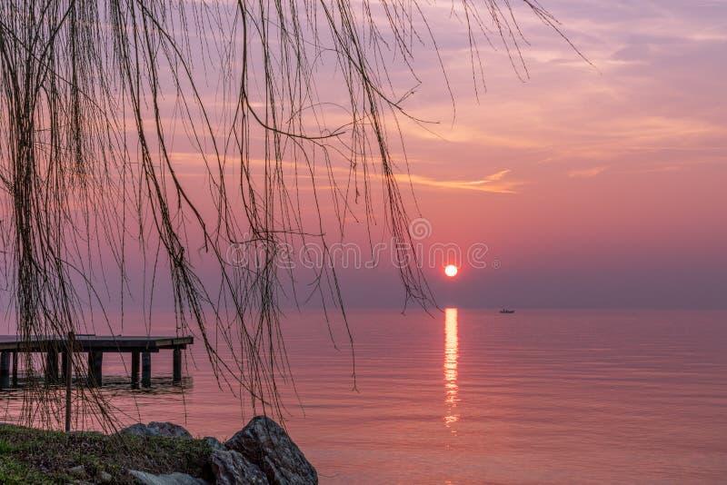 Bello tramonto porpora durante la nebbia sulla polizia del lago con una siluetta di una barca dei pescatori nei precedenti L'Ital fotografia stock libera da diritti