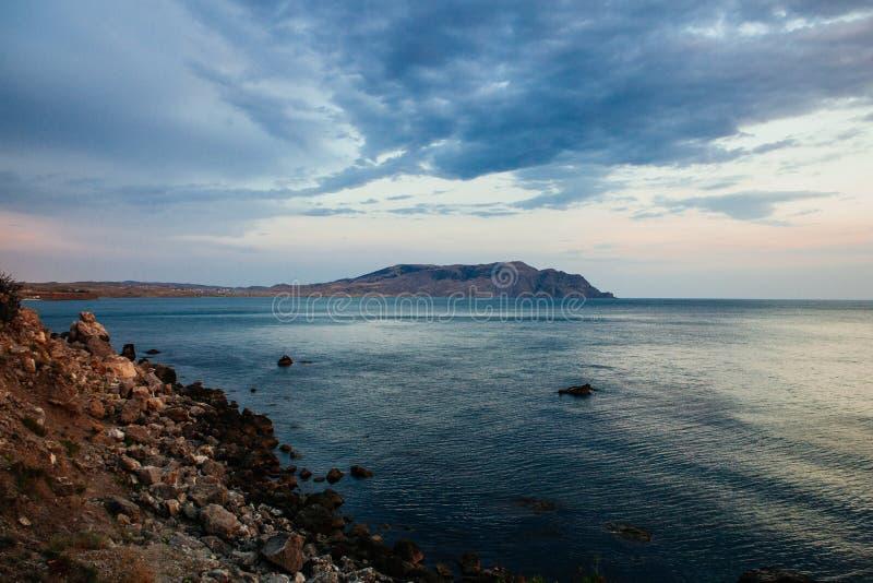 Bello tramonto, rocce e mare nella sera immagine stock